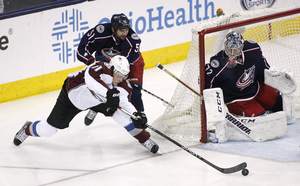 Photo - Columbus Blue Jackets' Fedor Tyutin (51) pushes Colorado Avalanche's Jamie McGinn (11) from behind as he tries to score on goalie Sergei Bobrovsky during the third period of an NHL hockey game, Tuesday, April 1, 2014, in Columbus, Ohio. (AP Photo/Mike Munden)