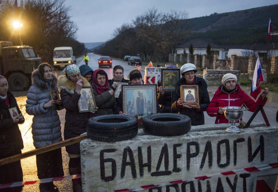 Photo - Pro-Russian activists hold up Orthodox icons at a checkpoint outside the Ukrainian Black Sea port of Sevastopol in the Crimea, Ukraine, Thursday, Feb. 27, 2014. The banner reads