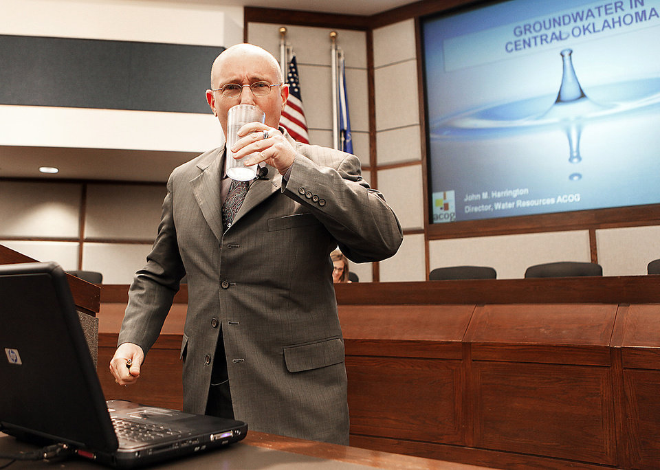 Photo - John Harrington, with the Association of Central Oklahoma Governments, takes a drink of water while leading a discussion Thursday night on Norman's future water needs. PHOTO BY STEVE SISNEY, THE OKLAHOMAN