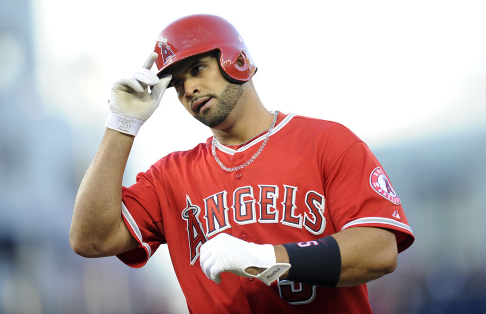 Photo - Los Angeles Angels' Albert Pujols (5) looks on after he grounded out during the first inning of a baseball game against the Washington Nationals, Monday, April 21, 2014, in Washington. (AP Photo/Nick Wass)