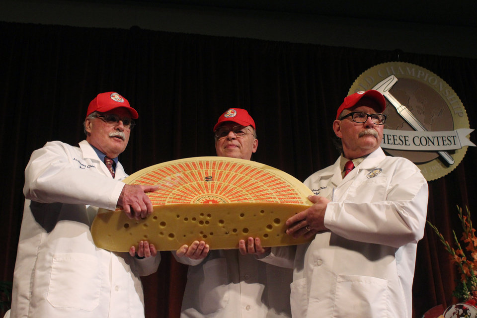 Photo - Three judges for the 2014 World Championship Cheese Contest hold the champion, a Swiss Emmentaler, Wednesday, March 19, 2014, in Madison, Wis. Cheesemaker Gerard Sinnesberger from Kaserei Sinnesberger in Gams, Switzerland, took top honors out of 2,615 entries from 22 countries. (AP Photo/Carrie Antlfinger)