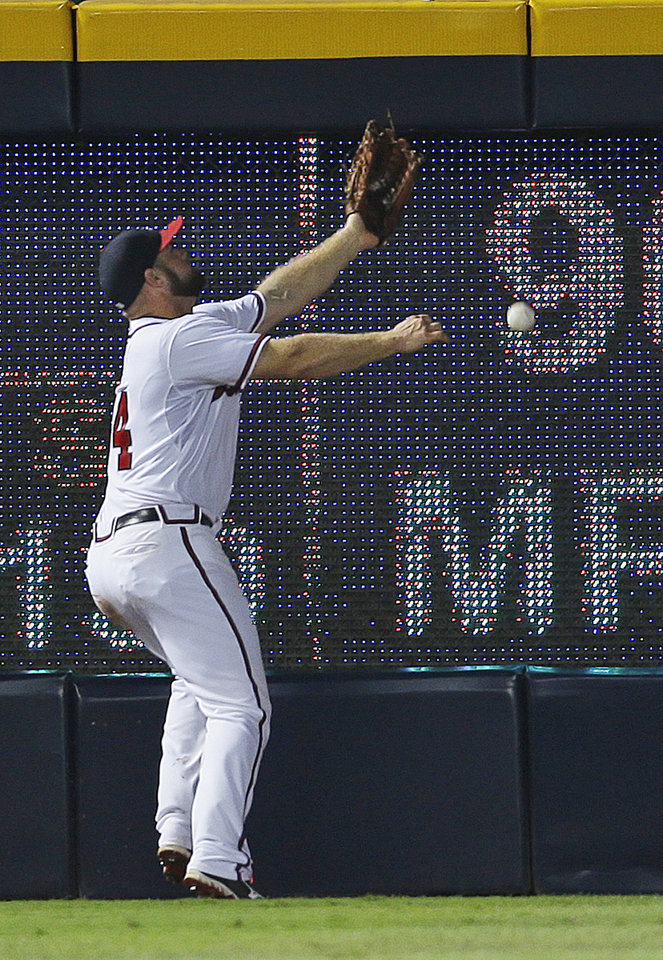 Atlanta Braves left fielder Evan Gattis can't make the play on ball hit for a triple by New York Mets batter Eric Young in the sixth inning of a baseball game Tuesday, Sept. 3, 2013 in Atlanta. (AP Photo/John Bazemore)