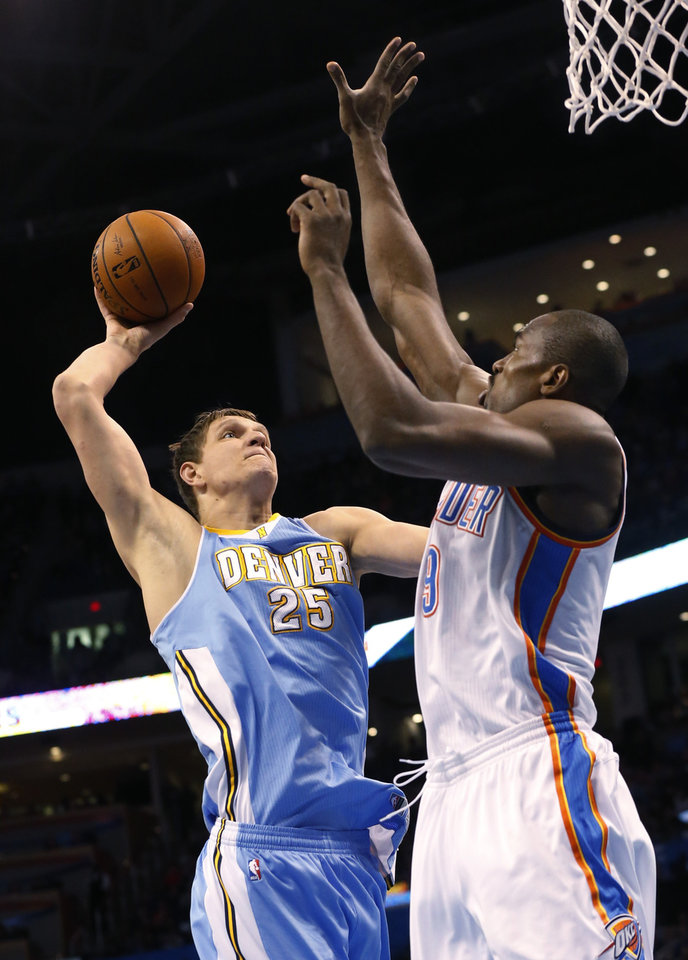 Photo - Denver Nuggets center Timofey Mozqov (25) shoots in front of Oklahoma City Thunder forward Serge Ibaka (9) in the first quarter of an NBA basketball game in Oklahoma City, Monday, March 24, 2014. (AP Photo/Sue Ogrocki)