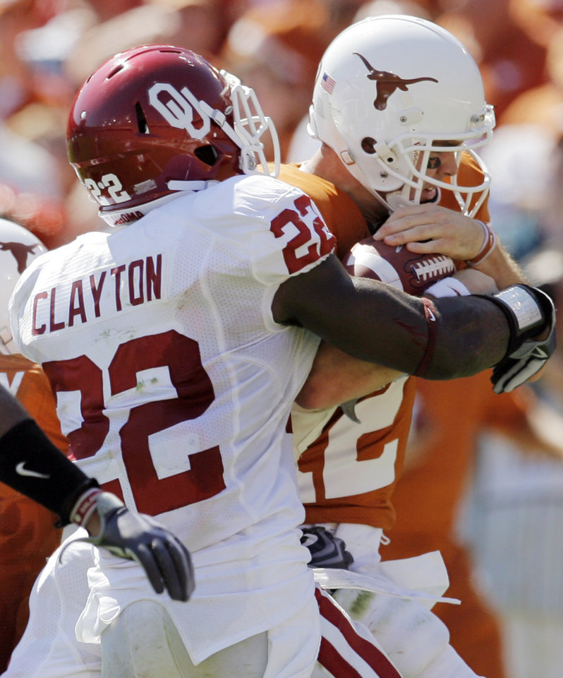 Photo - OU's Keenan Clayton (22) tries to strip the ball away from Texas quarterback Colt McCoy (12) during the Red River Rivalry college football game between the University of Oklahoma Sooners (OU) and the University of Texas Longhorns (UT) at the Cotton Bowl in Dallas, Texas, Saturday, Oct. 17, 2009. McCoy fumbled on the play. The fumble was recovered by OU. Photo by Nate Billings, The Oklahoman