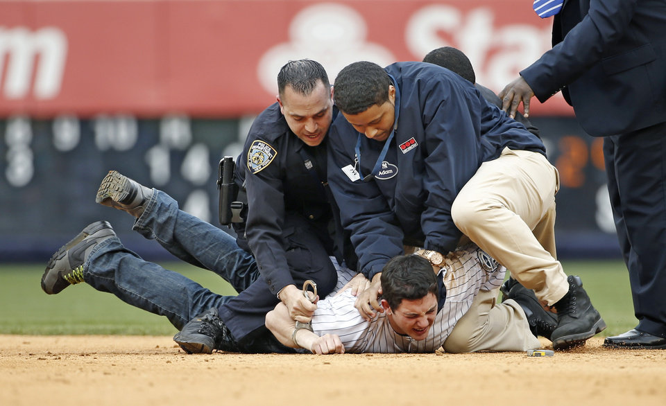 Photo - A police officer and a security officer tackle a fan who ran onto the field in the eighth inning of the Yankees 14-5 loss to the Baltimore Orioles during the MLB American League baseball game at Yankee Stadium in New York, Tuesday, April 8, 2014. Two fans made it onto the field behind second base and were tackled and escorted off the field as players watched. (AP Photo/Kathy Willens)