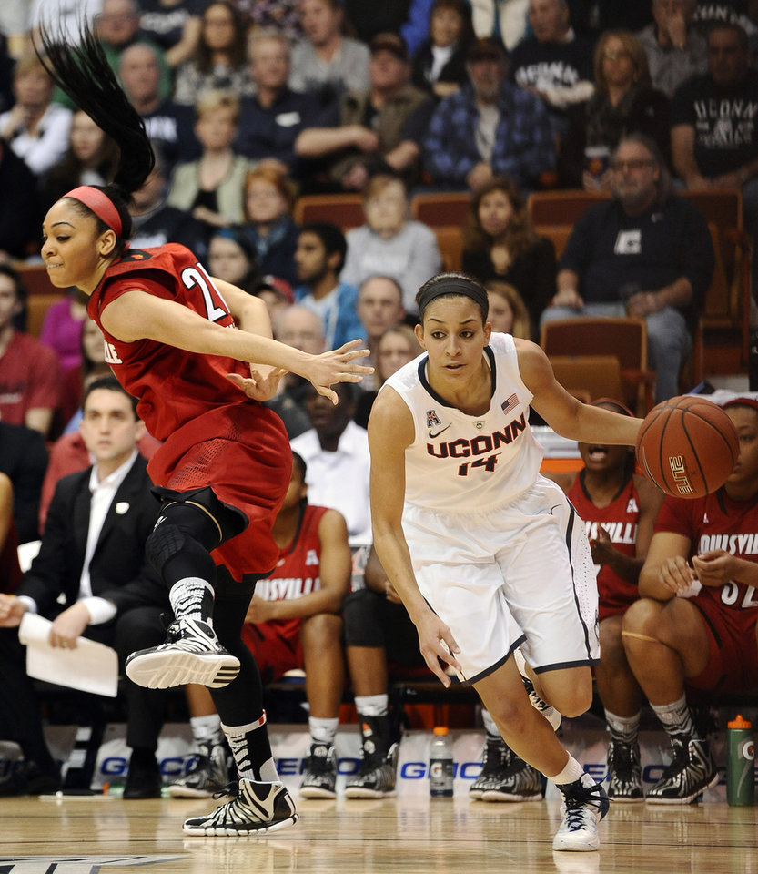 Photo - Connecticut's Bria Hartley, right, drives past  Louisville's Bria Smith, left, during the first half of an NCAA college basketball game in the finals of the American Athletic Conference women's basketball tournament, Monday, March 10, 2014, in Uncasville, Conn. (AP Photo/Jessica Hill)