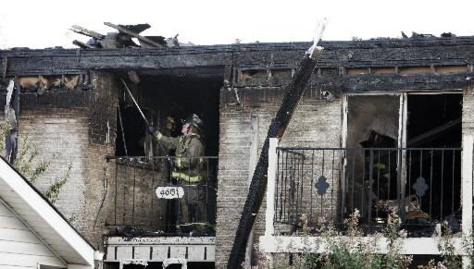 A fireman standing on a second floor balcony looking for hot spots after putting out a fire at the Ambassador House Apartments, 4607 N Pennsylvania Ave., in Oklahoma City Thursday, Sept. 19, 2013. Three people were injured in the four-alarm apartment fire. Photo by Paul B. Southerland, The Oklahoman