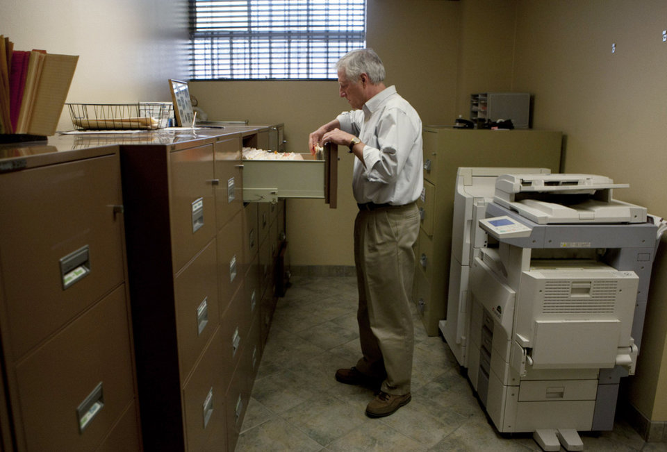 Photo - Steve Wyard, 61, a regional sales director of All Valley Washer Service, looks for files in his office recently in the Van Nuys section of Los Angeles. AP Photo  Jae C. Hong
