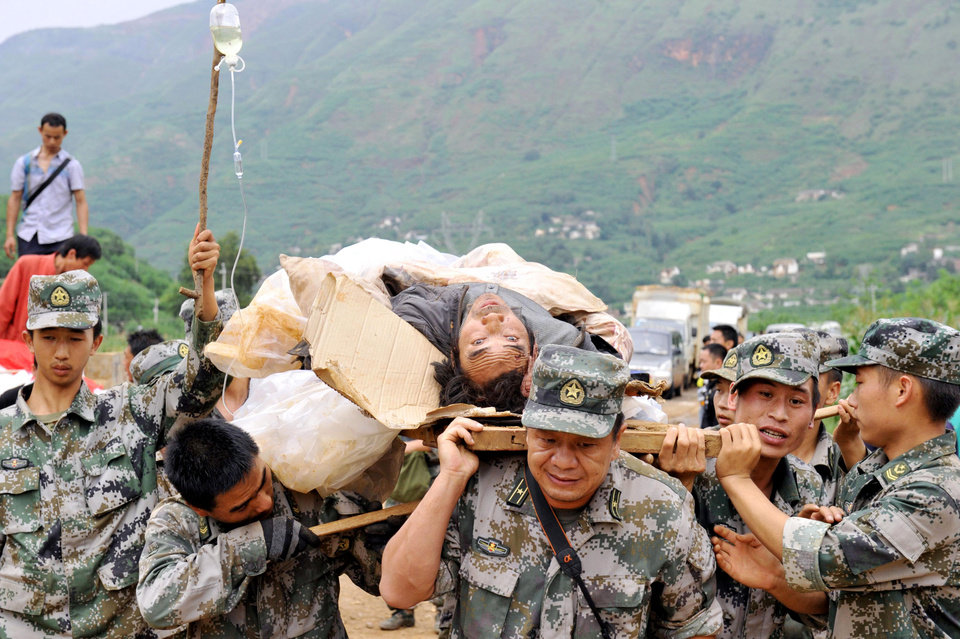 Photo - Rescuers carry an injured man during a rescue operation following Sunday's earthquake in Ludian county of Zhaotong city in southwest China's Yunnan Province, Monday, Aug. 4, 2014. Rescuers dug through shattered homes Monday looking for survivors of a strong earthquake in southern China's Yunnan province that killed hundreds and injured more than a thousand people. (AP Photo/Kyodo News) JAPAN OUT