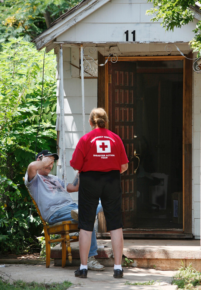 Photo - Carol Irwin, a volunteer with the American Red Cross, talks to Albert Ortega on the front porch of Ortega's home at 11 SW 27, on the west bank of Lighning Creek.  Ortega, who has lived in the house for five months, said he was in Tulsa visiting his daughter when flood waters surged into his home. He returned to his house about 2 Friday morning to find water still covering the floor, from front door to the back door. Irwin and another volunteer canvassed the neighborhood Friday, talking to residents and asking about their immediate needs. They told Ortega he could stay in a temporary shelter, but he declined, saying he wanted to