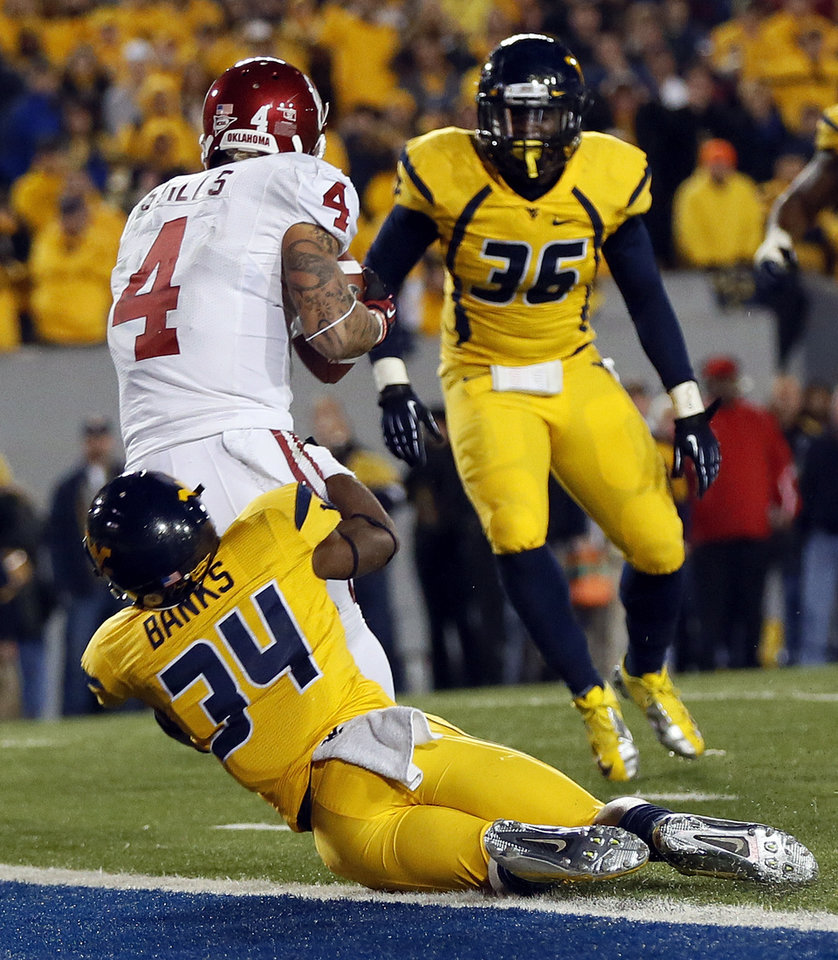 Photo - Oklahoma's Kenny Stills (4) catches the final touchdown for OU against West Virginia's Ishmael Banks (34) as Nick Kwiatkoski (35) looks on in the fourth quarter during a college football game between the University of Oklahoma and West Virginia University on Mountaineer Field at Milan Puskar Stadium in Morgantown, W. Va., Nov. 17, 2012. OU won, 50-49. Photo by Nate Billings, The Oklahoman
