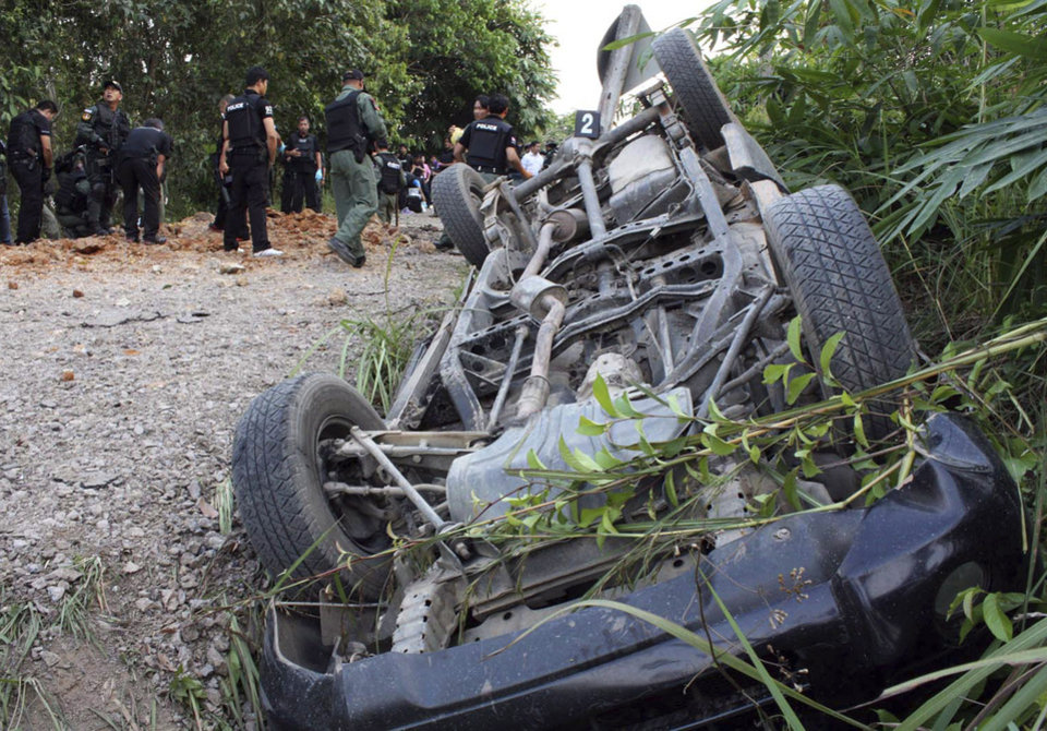 Thai officials examine the site near the wreckage of a pickup truck carrying Thai soldiers that was hit by a roadside bomb attack in Cho Airong district of Narathiwat province, southern Thailand Thursday, March 28, 2013. Suspected militants have killed three soldiers in the roadside attack in Thailand's insurgency-plagued south. The attack came just hours before peace talks between Thai officials and Muslim insurgents were to begin in neighboring Malaysia. (AP Photo/Ahmad Ramansiriwong)