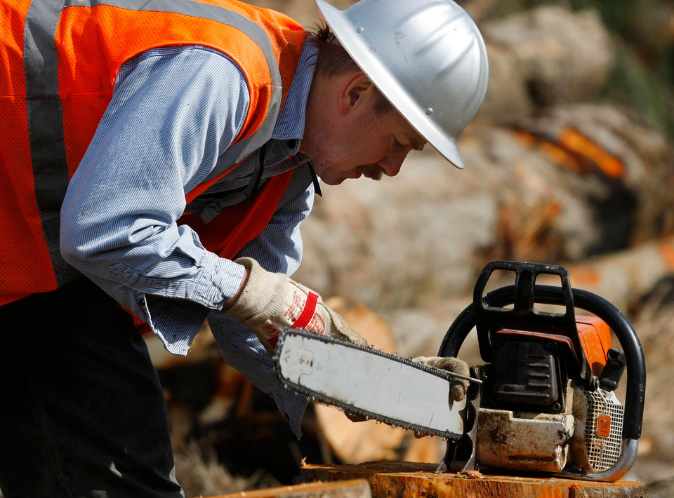 Photo - A volunteer logger sharpens his chainsaw at the Oso, Wash., mudslide site, Wednesday, April 2, 2014. (AP Photo/The Herald, Genna Martin)