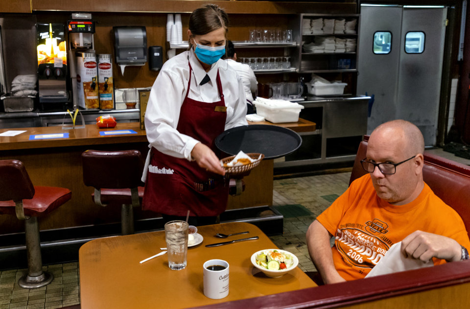 Photo - Waitress Tori Joyner serves lunch to customer Phil Hessel at Cattlemen's Steakhouse in Oklahoma City, Okla. on Friday, May 1, 2020. Cattlemen's and other restaurants begin their gradual reopening on Friday after being closed due to the Coronavirus Pandemic.[Chris Landsberger/The Oklahoman]