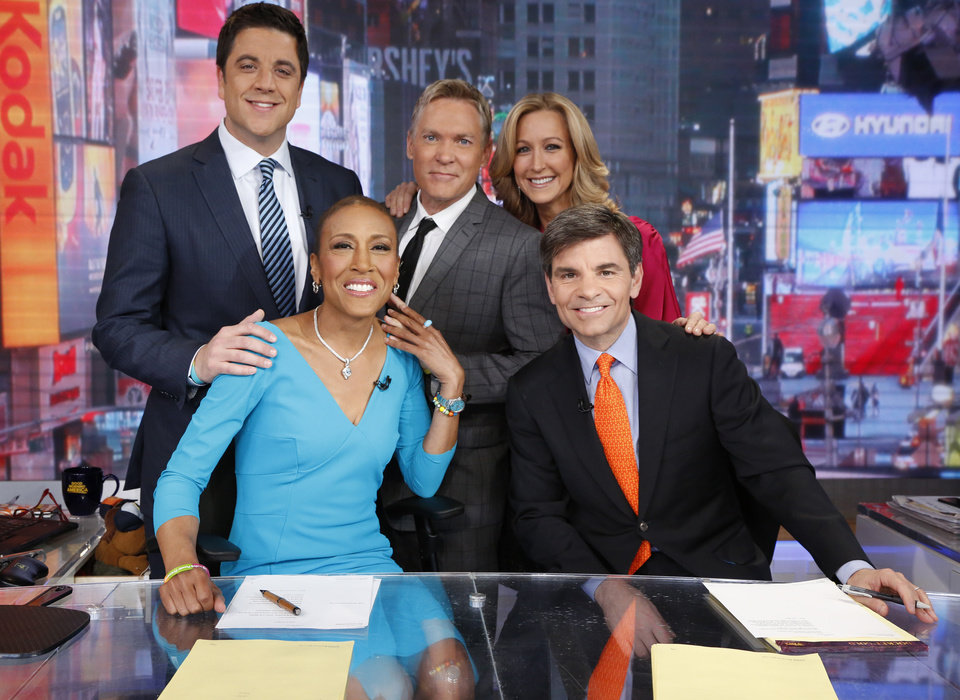 "This Feb. 20, 2013 photo released by ABC shows Robin Roberts, left,  George Stephanopoulos, (standing, from left) Josh Elliott, Sam Champion, and Lara Spencer, on the set of ""Good Morning America"" in New York.   Five months after undergoing a bone marrow transplant, Roberts is back on television in the morning.  Roberts said Wednesday she'd been waiting 174 days ""to say this, good morning America."" The morning-show host is recovering from MDS, a blood and bone marrow disease.  (AP Photo/ABC, Heidi Gutman)"