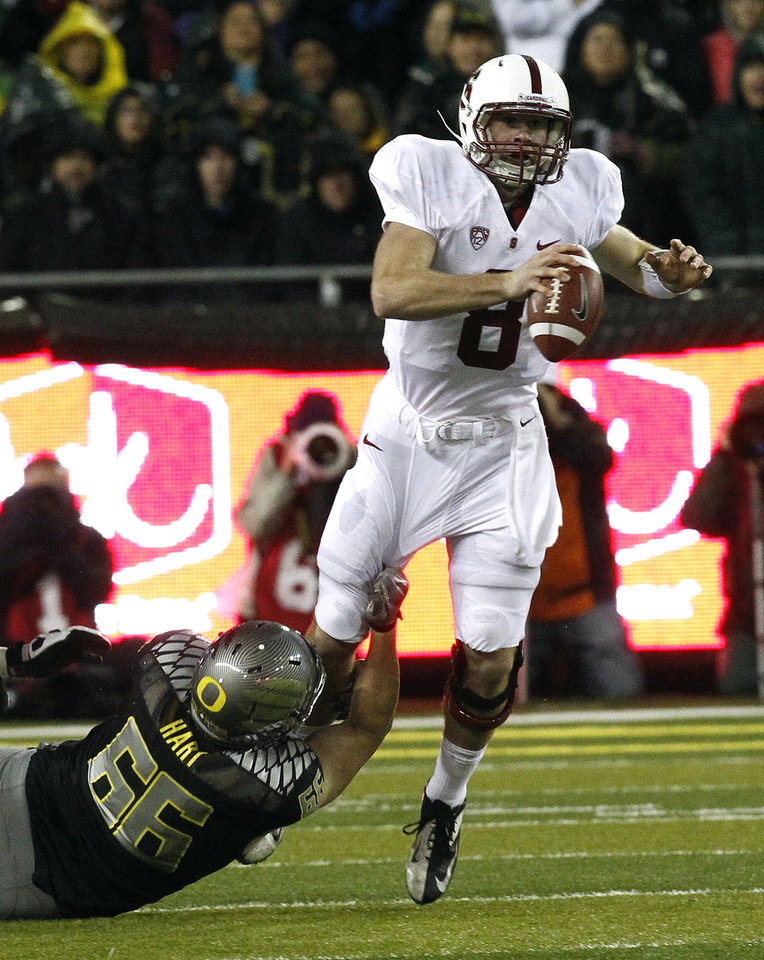 Photo -   Stanford quarterback Kevin Hogan, right, is tackled by Oregon defender Taylor Hart during the first half of an NCAA college football game in Eugene, Ore., Saturday, Nov. 17, 2012.(AP Photo/Don Ryan)