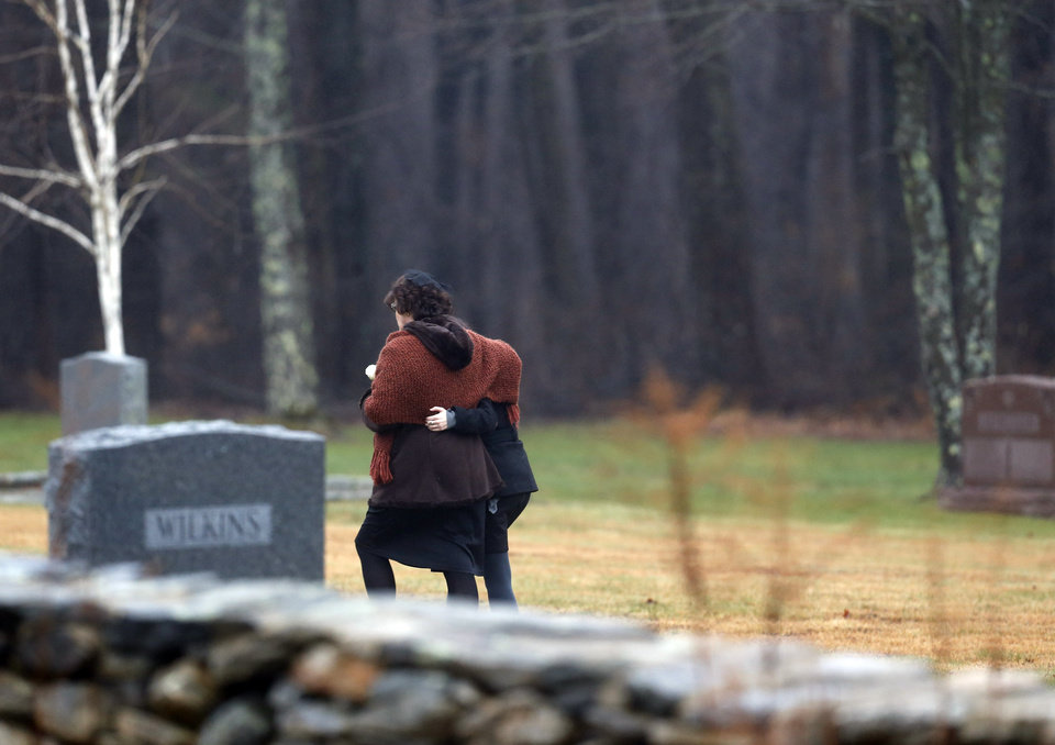 Photo - Veronique Pozner, left, embraces a young girl as she arrives at B'nai Israel Cemetery for burial services for her 6-year-old son Noah Pozner, Monday, Dec. 17, 2012, in Monroe, Conn. Noah Pozner was killed when Adam Lanza walked into Sandy Hook Elementary School in Newtown, Conn., Friday and opened fire, killing 26 people, including 20 children, before killing himself. (AP Photo/Julio Cortez) ORG XMIT: CTJC119