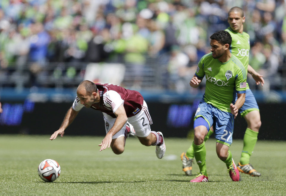 Photo - Colorado Rapids' Nick LaBrocca (2) goes down on a play involving Seattle Sounders' Lamar Neagle, second from right, Saturday, April 26, 2014, in the first half of an MLS soccer match in Seattle. (AP Photo/Ted S. Warren)