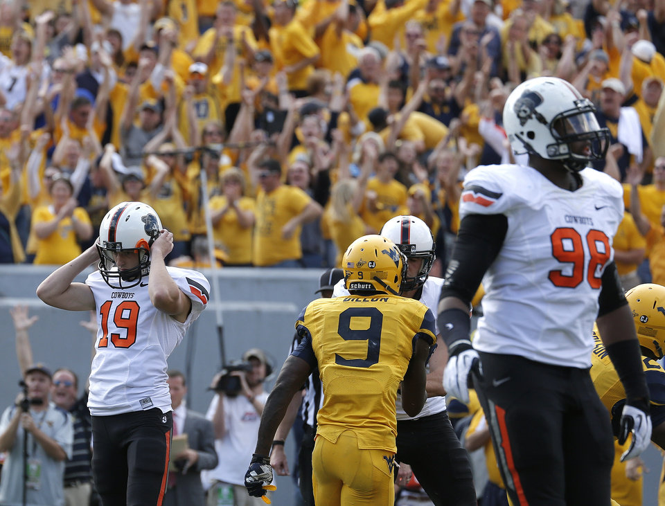 Photo - Oklahoma State's Ben Grogan (19) reacts after missing a tying field goal late in the fourth quarter of a college football game between the Oklahoma State University and West Virginia University on Mountaineer Field at Milan Puskar Stadium in Morgantown, W. Va.,   Saturday, Sept. 28, 2013. Photo by Sarah Phipps, The Oklahoman