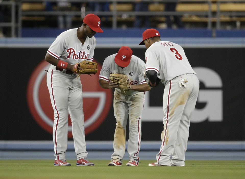 Photo - Philadelphia Phillies' Domonic Brown, from left, Ben Revere, Marlon Byrd bow to each other as they celebrate their team's 10th inning 3-2 win against the Los Angeles Dodgers after a baseball game on Tuesday, April 22, 2014, in Los Angeles. (AP Photo/Jae C. Hong)