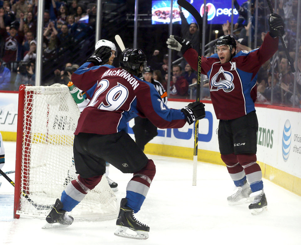 Photo - Colorado Avalanche center Nathan MacKinnon, left, celebrates with teammate Paul Stastny after his goal against the San Jose Sharks in the first period of an NHL hockey game on Saturday, March 29, 2014, in Denver. (AP Photo/David Zalubowski)