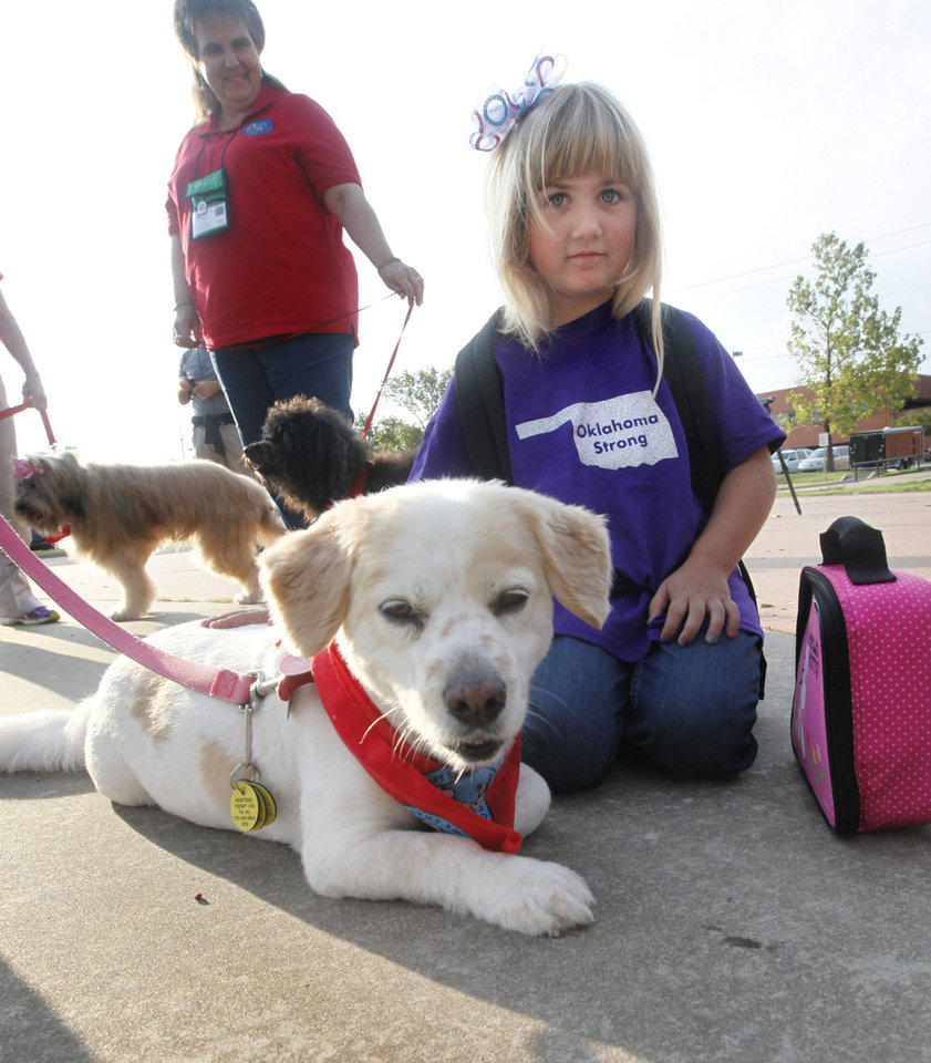Photo - First grader Kali Dooley pets therapy dog, Ginger, as Plaza Towers Elementary School students begin their first day of classes Friday in their temporary location at Central Junior High in Moore.  Photo by Paul Hellstern, The Oklahoman  PAUL HELLSTERN - Oklahoman