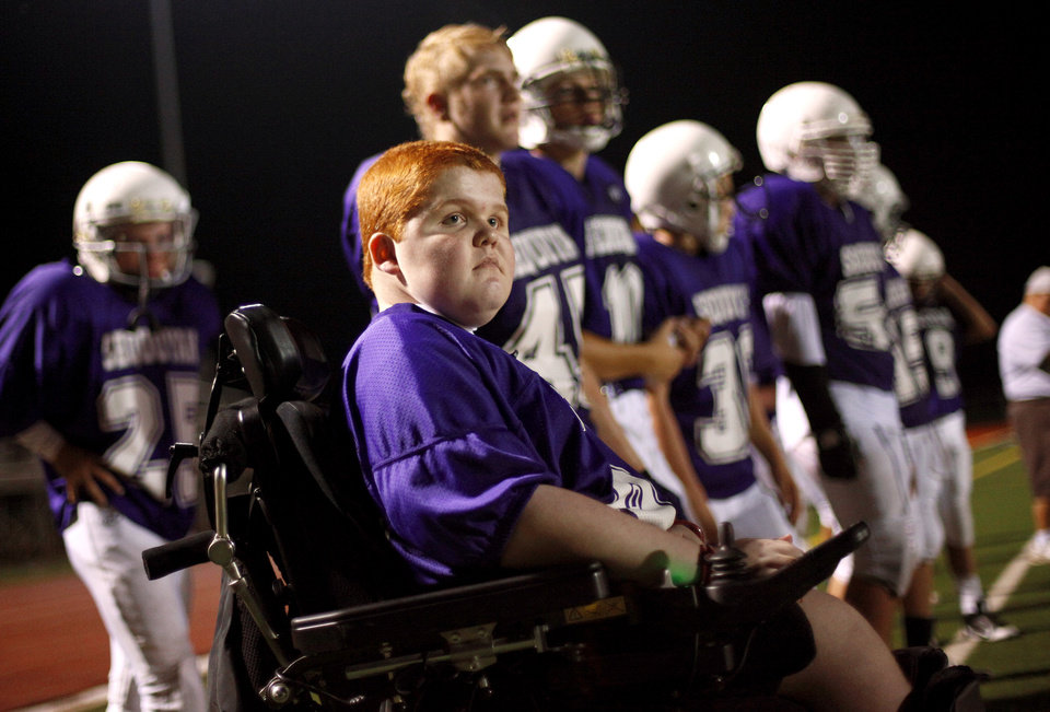 Photo - Keegan Erbst watches from the sidelines during a Sequoyah Middle School football team as they huddle up during halftime of their game, Thursday, September 27, 2012. Keegan, who has muscular dystrophy and is confined to a wheelchair, got involved with the team after players Lucas Coker, Colton James, and Parker Tumleson, suggested it to the coach.  Photo by Bryan Terry, The Oklahoman