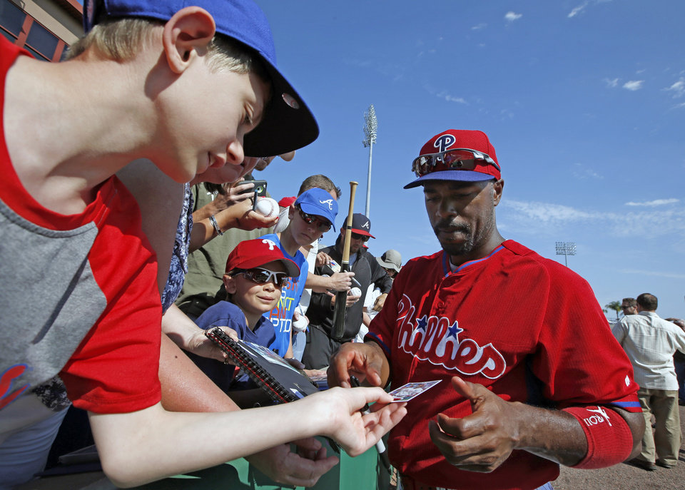 Photo - Philadelphia Phillies' Jimmy Rollins, right, autographs a baseball trading card for a young fan before a spring exhibition baseball game in Clearwater, Fla., Monday, March 10, 2014.  (AP Photo/Kathy Willens)