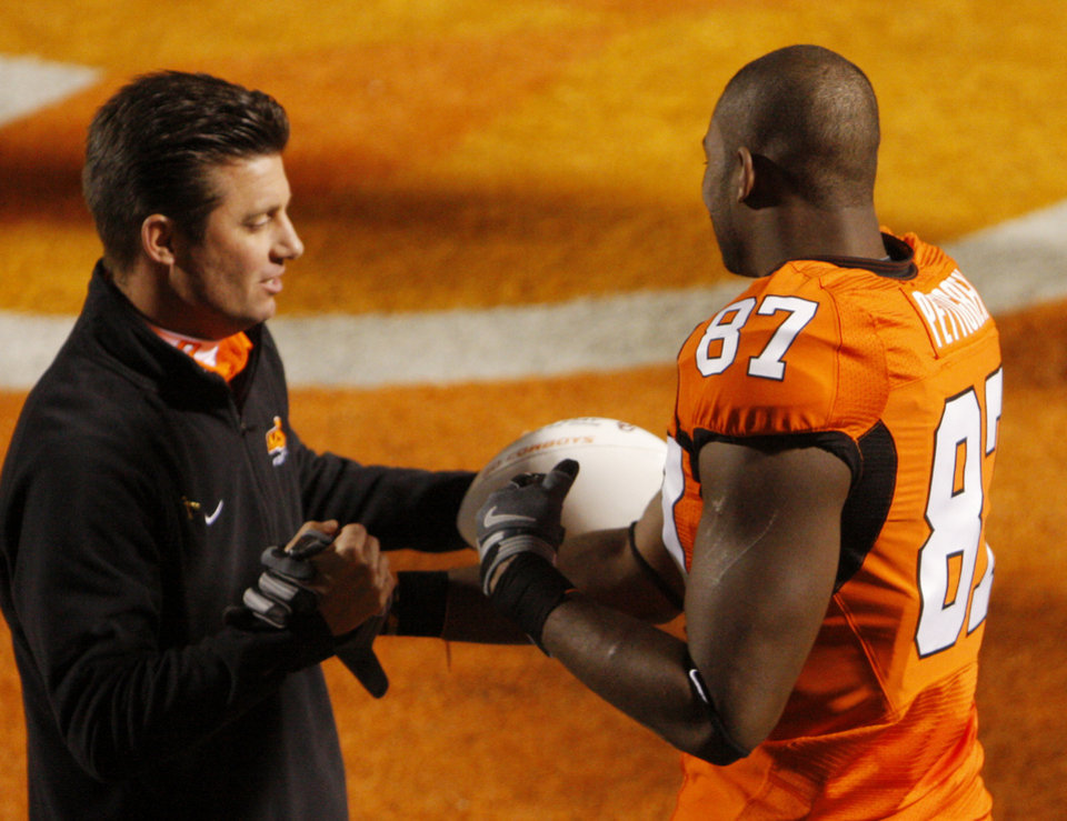 Photo - Mike Gundy gives Brandon Pettigrew a game ball on senior day before the college football game between the University of Oklahoma Sooners (OU) and Oklahoma State University Cowboys (OSU) at Boone Pickens Stadium on Saturday, Nov. 29, 2008, in Stillwater, Okla. STAFF PHOTO BY DOUG HOKE