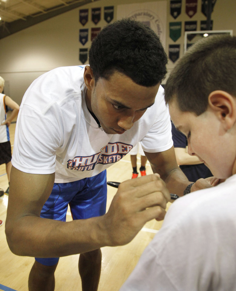 Photo - Oklahoma City Thunder forward Josh Huestis autographs the T-shirt of 11 year old Jerry Broughton during a visit to this week's Thunder Youth Basketball camp at Casady School in Oklahoma City, OK, Thursday, July 17, 2014,  Photo by Paul Hellstern, The Oklahoman