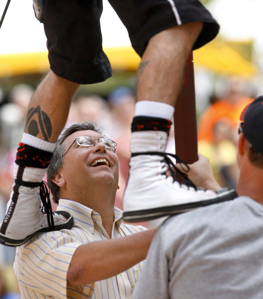 "Members of the audience, including Darrell Beavers of Oklahoma City,  help Al Millar down from the 12-foot-tall Chinese pole after his act. A comedian, contortionist and daredevil known as ""The Human Knot,"" Millar, 34, is the official street performer at the 2012 Festival of the Arts. Photo by Jim Beckel, The Oklahoman <strong>Jim Beckel - THE OKLAHOMAN</strong>"