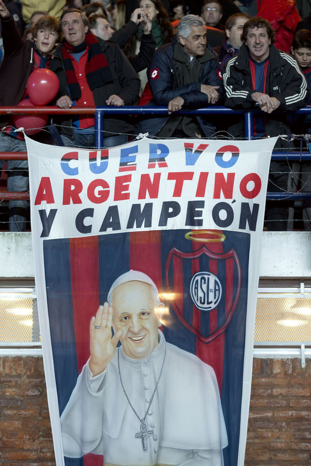 Photo - Fans of Argentina's San Lorenzo stand next to a banner of Pope Francis before the start of a Copa Libertadores final soccer match against Paraguay's Nacional in Buenos Aires, Argentina,  Wednesday, Aug. 13, 2014. (AP Photo/Victor R. Caivano)