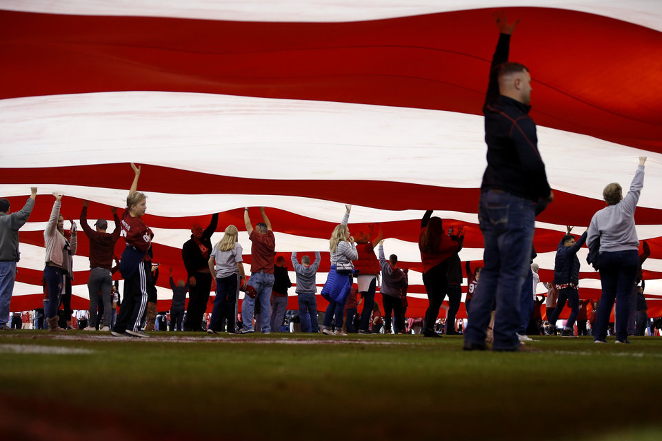 Photo - Volunteers raise a large American flag before an NCAA football game between the University of Oklahoma Sooners (OU) and the Iowa State University Cyclones at Gaylord Family-Oklahoma Memorial Stadium in Norman, Okla., Saturday, Nov. 9, 2019. [Bryan Terry/The Oklahoman]