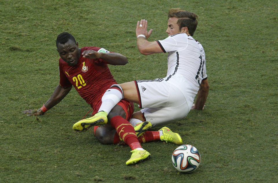 Photo - Ghana's Kwadwo Asamoah, left, and Germany's Mario Goetze vie for the ball during the group G World Cup soccer match between Germany and Ghana at the Arena Castelao in Fortaleza, Brazil, Saturday, June 21, 2014. (AP Photo/Themba Hadebe)
