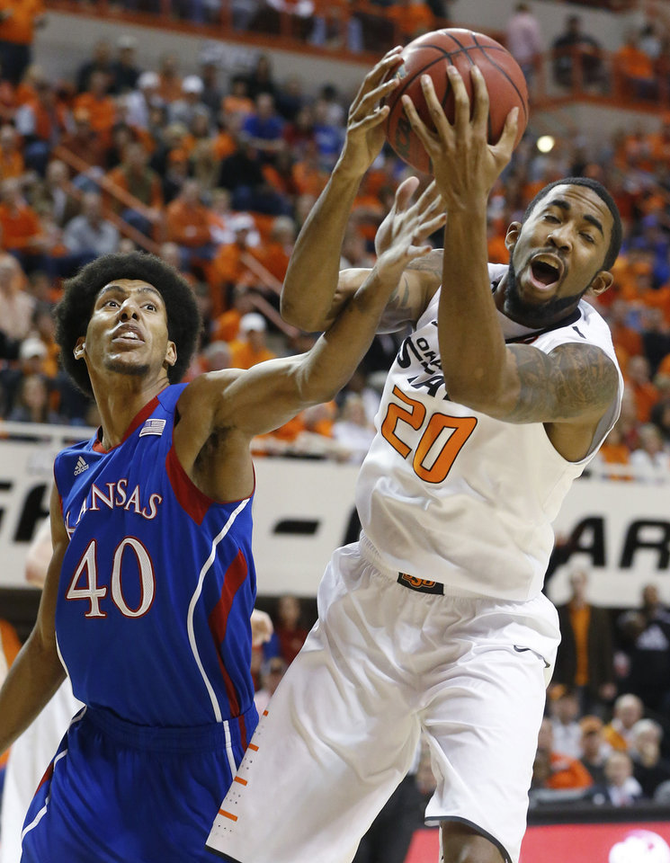 Oklahoma State forward Michael Cobbins (20) grabs a rebound in front of Kansas forward Kevin Young (40) during the first half of an NCAA college basketball game in Stillwater, Okla., Wednesday, Feb. 20, 2013. (AP Photo/Sue Ogrocki)