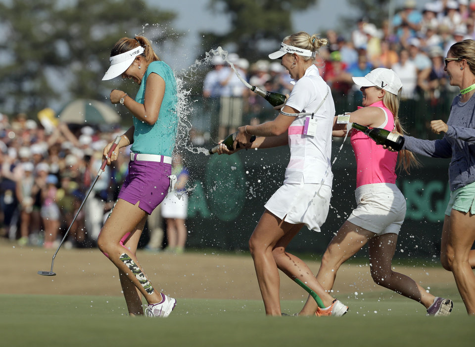Photo - Michelle Wie, left, is doused by fellow players after winning the U.S. Women's Open golf tournament in Pinehurst, N.C., Sunday, June 22, 2014. (AP Photo/Chuck Burton)