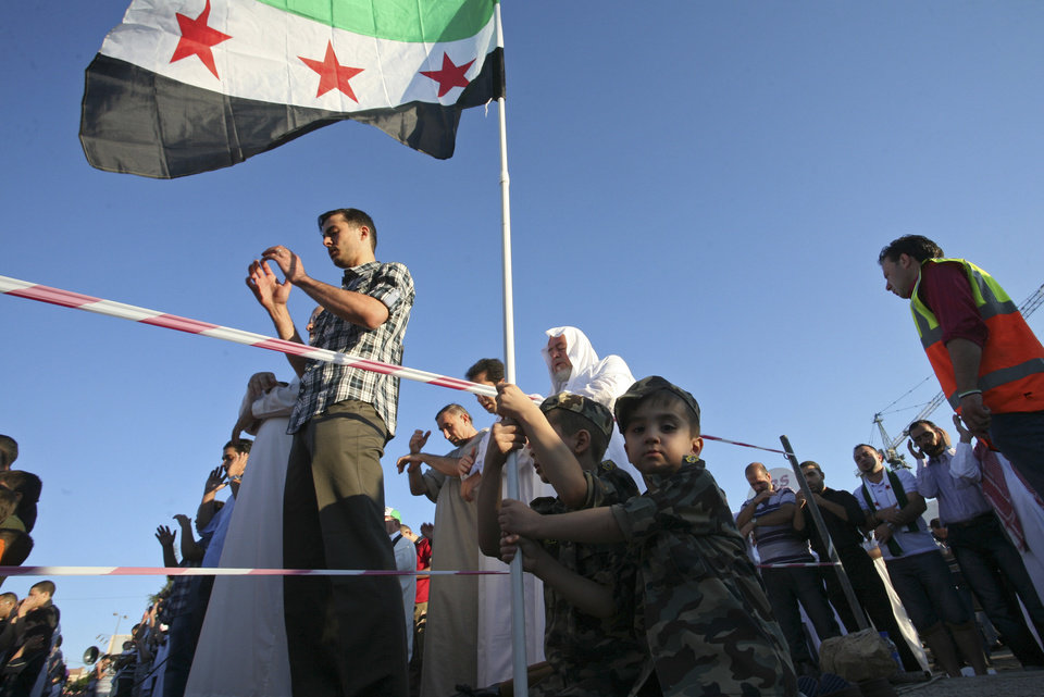 Photo -   Two Syrian boys wearing uniforms of the rebel Free Syrian Army wave the revolutionary Syrian flag, during Eid al-Fitr prayer, in front of the Syrian embassy, in Amman, Jordan, Sunday, Aug. 19, 2012. Muslims around the world celebrate Eid al-Fitr, marking the end of Ramadan, the Muslim calendar's ninth and holiest month during which followers are required to abstain from food and drink from dawn to dusk. (AP Photo/Mohammad Hannon)