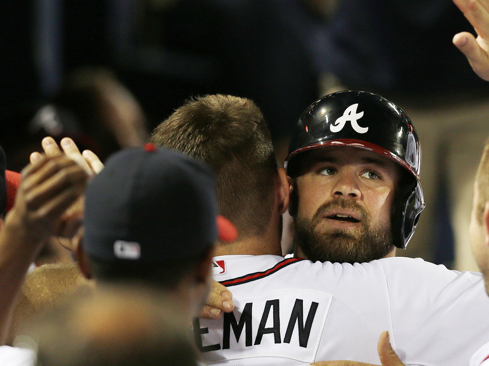 Atlanta Braves' Freddie Freeman hugs Evan Gattis, right, after Gattis hit a solo home run in the seventh inning of a baseball game against the New York Mets Tuesday, Sept. 3, 2013 in Atlanta. (AP Photo/John Bazemore)