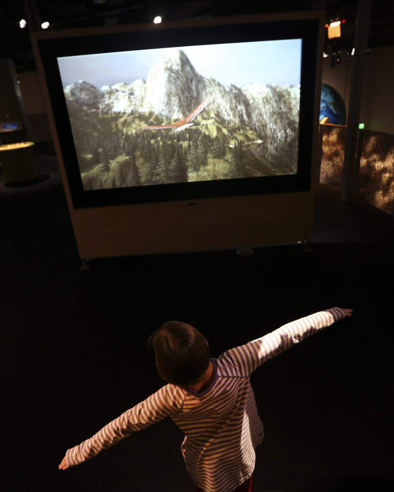 Emma Fisk spreads her arms like wings rto control a virtual bird while using an interactive display that simulates bird flight at the Perot Museum of Nature and Science during a media preview in Dallas, Wednesday, Nov. 14, 2012. The museum set to open Dec. 1 was named for billionaire former presidential candidate Ross Perot and his wife, Margot, after their five children made a $50 million gift in honor of them. (AP Photo/LM Otero)