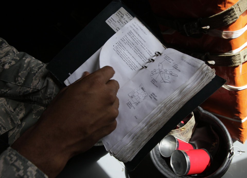In this Aug. 14, 2012 photo, a ground crew member looks at a service manual in a U.S. Air Force KC-135 Stratotanker, which was built in 1958, at Kadena Air Base on Japan's southwestern island of Okinawa. For decades, the U.S. Air Force has grown accustomed to such superlatives as unrivaled and unbeatable. Now some of its key aircraft are being described with terms like decrepit. (AP Photo/Greg Baker)