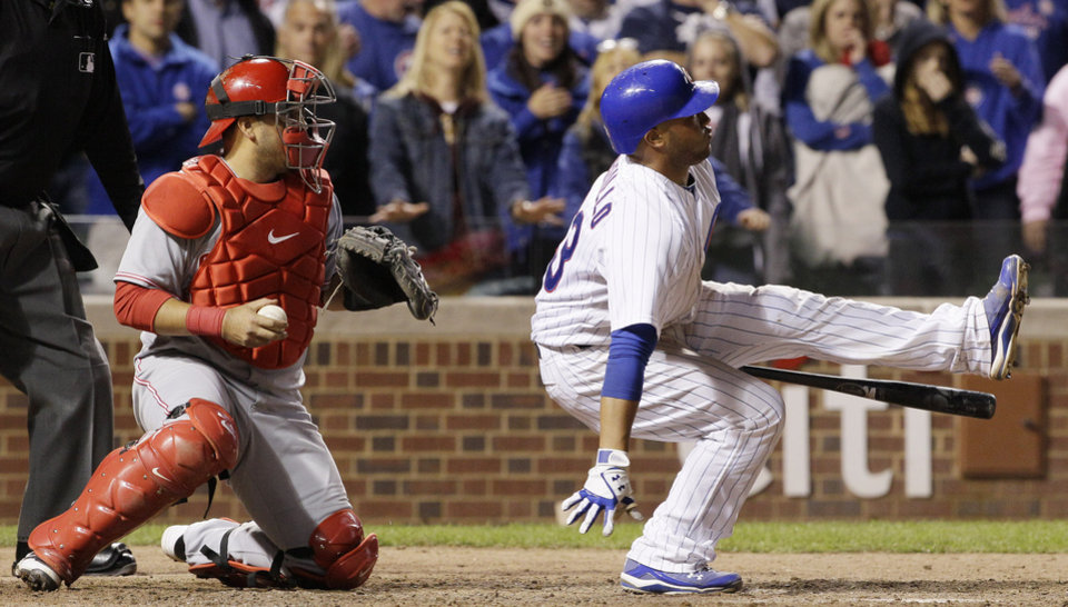 Photo -   Chicago Cubs' Welington Castillo, right, falls down after striking out as Cincinnati Reds catcher Dioner Navarro, left, looks on during the 10th inning of a baseball game in Chicago, Wednesday, Sept. 19, 2012. (AP Photo/Nam Y. Huh)