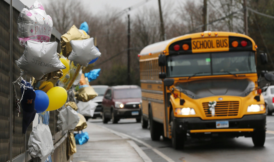 FILE - In this Dec. 18, 2012 file photo, a school bus rolls toward a memorial in Newtown, Conn., for victims of the Sandy Hook Elementary School shooting. Nearly three weeks after the shooting rampage, classes are starting Thursday, Jan. 3, 2013 for the Sandy Hook students at a repurposed school in the neighboring town of Monroe, where the students' desks have been taken along with backpacks and other belongings that were left behind in the chaos following the shooting on Dec. 14. (AP Photo/Charles Krupa, File)