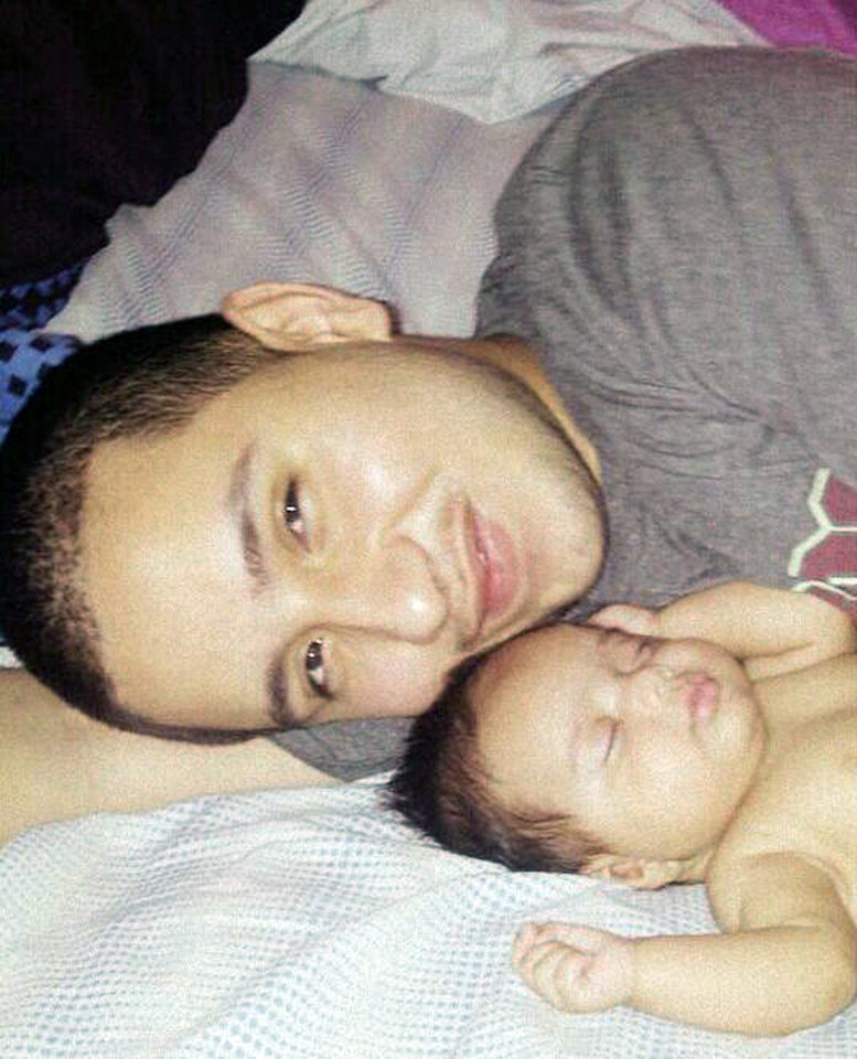 Photo - This undated photo provided by Felicia Leija shows Jose Banda, 20, with his newborn daughter Alisa. Authorities say Banda was fatally shot in December 2012 minutes after he slammed into a truck that was being pushed by a father and his two sons after the vehicle had broken down. The two boys were killed in the alcohol-related accident. Investigators allege the boys' father, David Barajas, shot Banda. Barajas' trial is set to begin Monday, Aug. 18.  (AP Photo/Felicia Leija)