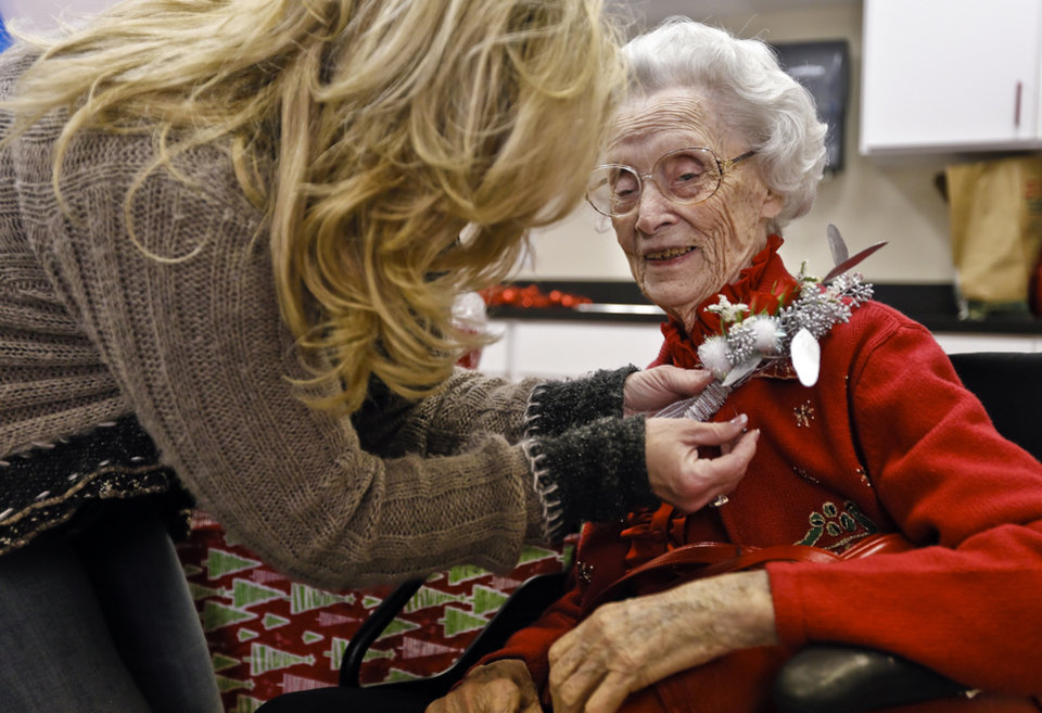 Leisa Davis pins a corsage to the sweater of Ora E. Holland during her early birthday celebration at Heritage Assisted Living Center on Saturday, Dec. 22, 2012, in Oklahoma City, Okla. Holland will celebrate her 112th birthday on Dec. 24, 2012.   Photo by Chris Landsberger, The Oklahoman
