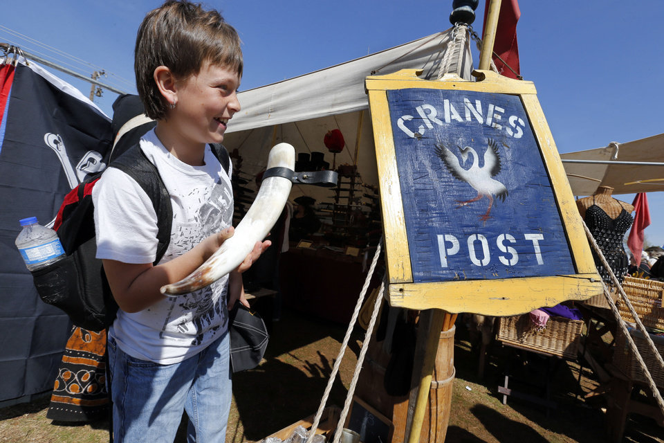 Dakota Reed, a Ninnekah sixth-grade student, checks out the merchandise during the Medieval Fair in Norman. Photo by Steve Sisney, The Oklahoman STEVE SISNEY