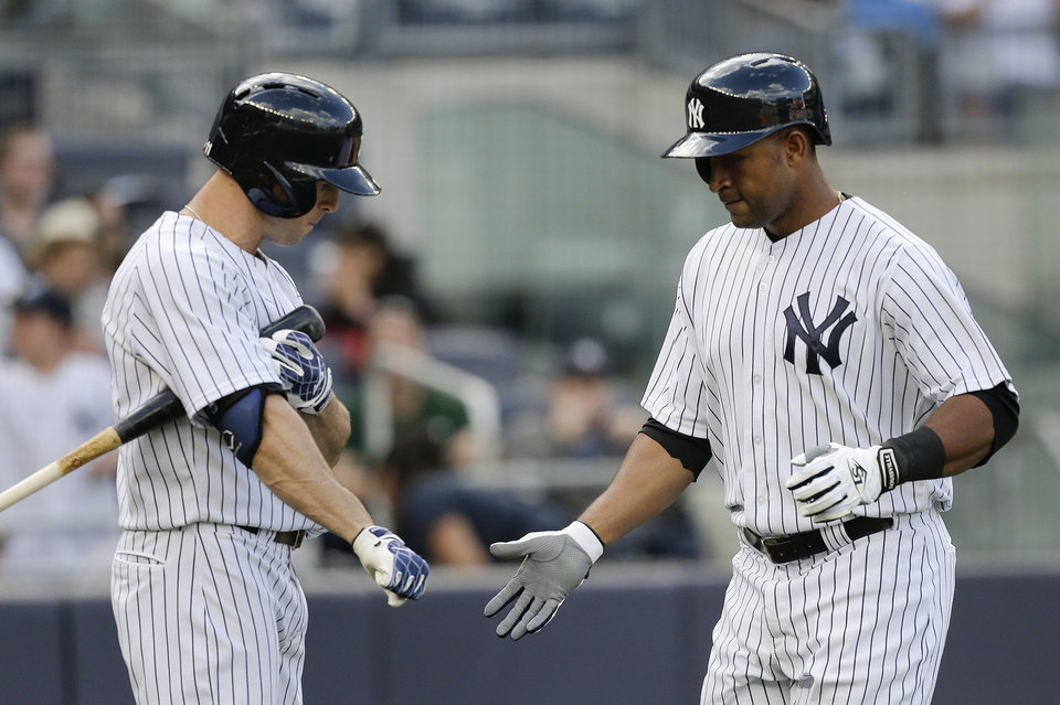 Photo - New York Yankees' Zoilo Almonte , right, is greeted at home plate by Brett Gardner after hitting a solo home run against the Pittsburgh Pirates during the third inning of a baseball game, Saturday, May 17, 2014, in New York. (AP Photo/Julie Jacobson)