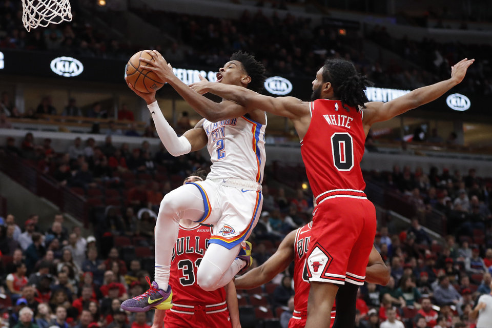 Photo - Chicago Bulls' Coby White (0) fouls Oklahoma City Thunder's Shai Gilgeous-Alexander as he drives to the basket during the first half of an NBA basketball game Tuesday, Feb. 25, 2020, in Chicago. (AP Photo/Charles Rex Arbogast)