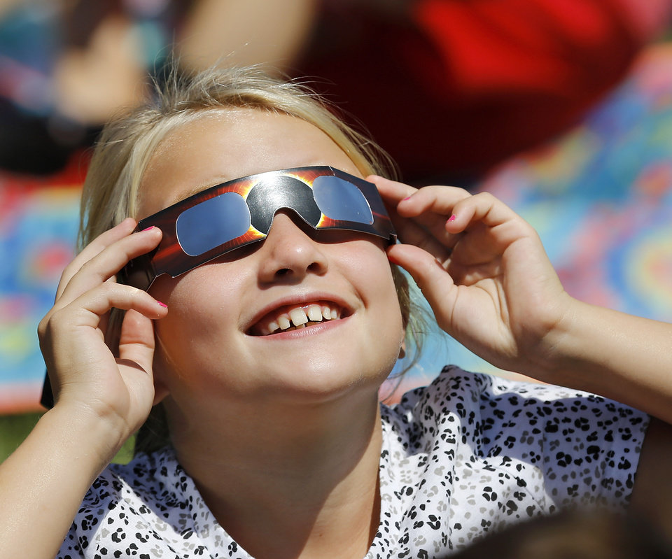 Photo - Fourth grader Taryn Jones smiles as she takes her first look at the eclipse. The entire student body, faculty and some parents gathered in a field on the north side of  James Griffith Intermediate School to view the solar eclipse Monday afternoon, Aug. 21, 2017.  Special glasses with very dark lenses were purchased to allow teachers and students to safely view the celestial event. Children were served  Moon Pies as a snack to enjoy while viewing the eclipse. Photo by Jim Beckel, The Oklahoman
