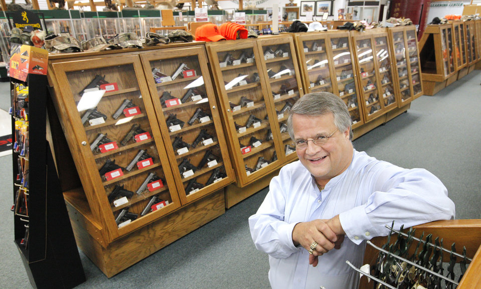 Photo - Miles Hall, founder and president of H & H Shooting Sports, in front of display cases of handguns inside H & H Shooting Sports, 400 S Vermont, in Oklahoma City Wednesday, June 25, 2014.  Photo by Paul B. Southerland, The Oklahoman
