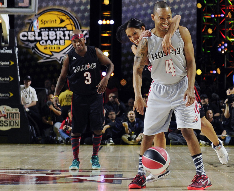 "Terrence Jenkins (4), from ""E! News,"" is fouled by ""Entertainment Tonight""'s Rocsi Diaz as Ne-Yo (3) looks on in the first quarter of the NBA All-Star celebrity basketball game Friday, Feb. 15, 2013, in Houston. (AP Photo/Pat Sullivan)"
